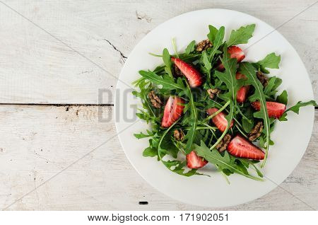 Fresh salad with arugula strawberries and nuts served on white plate on rustic wooden table with place for text. Healthy organic diet food concept. Top view. Copy space.