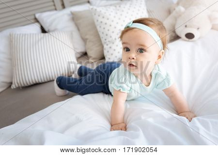 Exploring this world. Cute curious little girl lying on the bed in the bedroom and looking away while expressing interest
