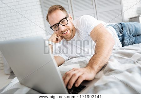 My favorite job. Charismatic smiling cheerful man lying on the bed and using the laptop while expressing interest and surfing the Internet