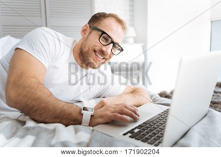 Enjoyable working hours . Joyful smiling bearded man lying on the bed and using the laptop while expressing interest and working