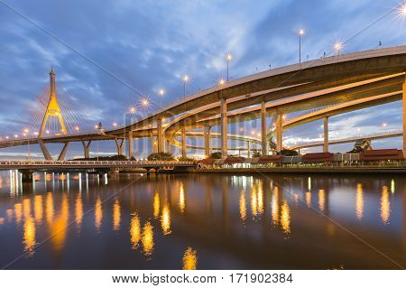 Suspension bridge connect to highway againts twilight sky background and water reflection Bangkok Thailand