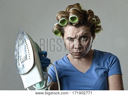 young attractive woman or housewife sad bored and stressed holding iron angry and frustrated in domestic work housekeeping and housework concept isolated background