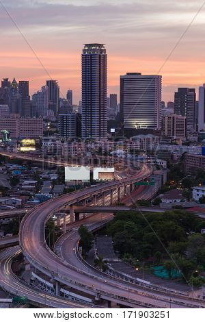 Highway intersection with city office building and dramatic after sunset sky background Bangkok Thailand