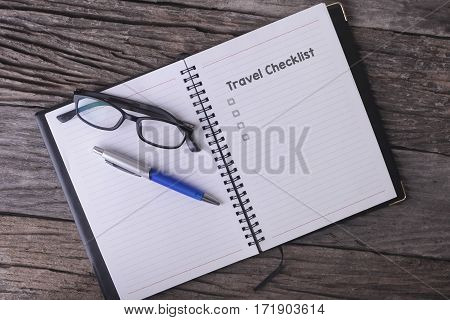 Conceptual,notebook On A Wooden Table. Open Diary, Glasses And Pen With Travel Checklist Word.