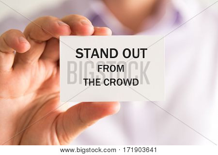 Businessman Holding Stand Out From The Crowd Card