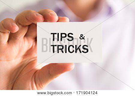 Businessman Holding Card With Text Tips And Tricks