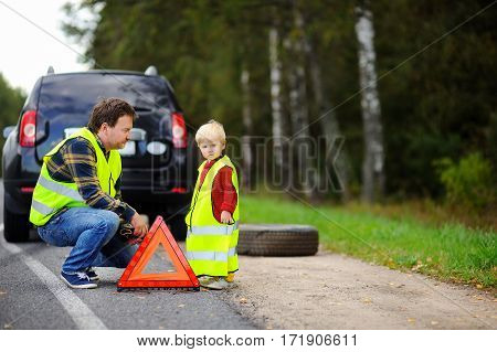 Father And His Little Son Repairing Car And Changing Wheel Together