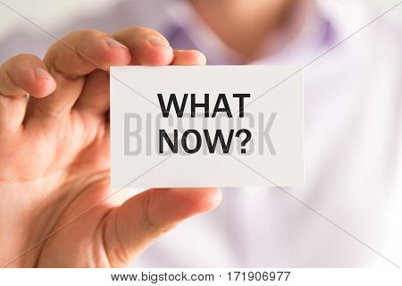 Businessman Holding A Card With Text What Now