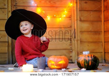 Cute Little Wizard Playing With Halloween Pumpkins