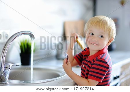 Cute Toddler Boy Washing Dishes In Domestic Kitchen