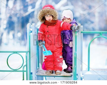 Little Children In Winter Clothes Having Fun On Playground At The Snowy Winter Day