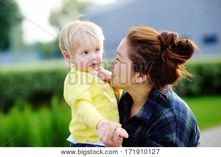 Young loving asian women with cute caucasian toddler boy. Babysitting concept