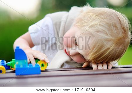 Toddler boy playing with toy train outdoors at warm summer day. Toys for little children