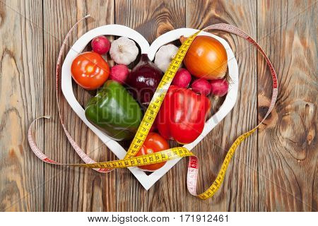 Sport and diet. Vegetables centimeter. Peppers tomatoes garlic onions and radishes in the heart on rustic background