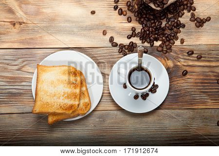 Breakfast concept - cup of black coffee with toasts and apricot jam at the background