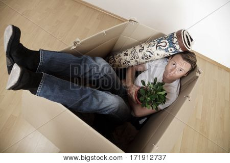 a young man and his belongings, stuffed into a crate. maybe he was thrown out of his apartment