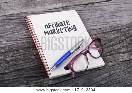 Note With Affiliate Marketing On The Wooden Background.