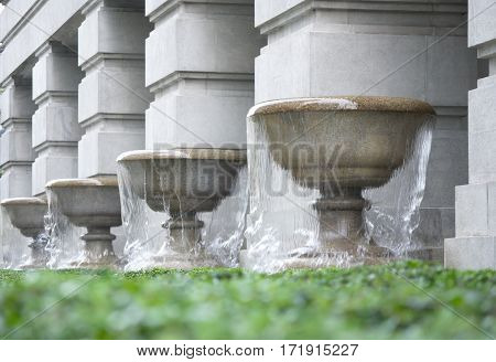 Four Fountains on a grass base with gray pillars background