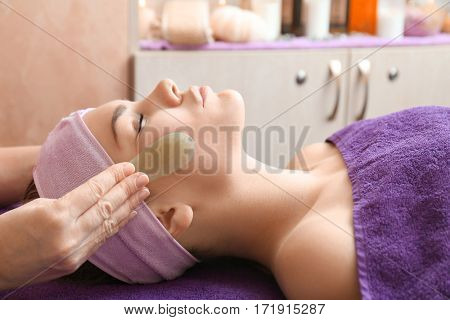 Face massage with jade stones in spa center