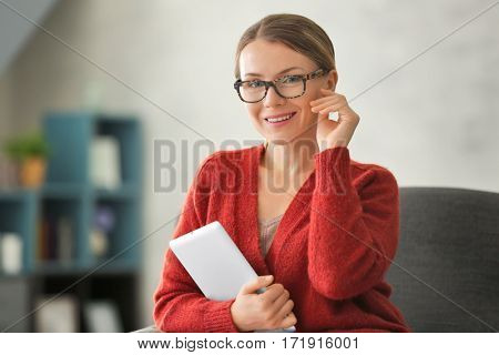 Young woman with tablet sitting on armchair