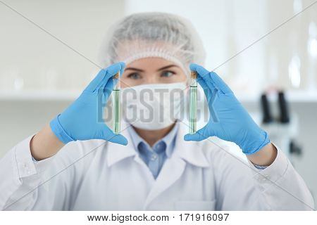 Scientist holding test tubes with samples in laboratory