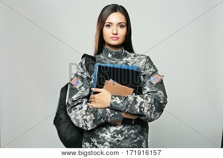 Pretty female cadet of military school on grey background