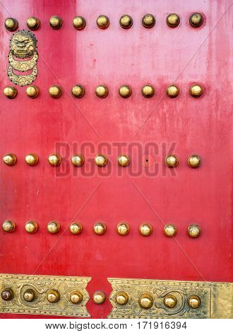 Beijing, China - Oct 30, 2016: Royal red studded door, handle and ornate plate to the Hall of Supreme Harmony (Taihedian), Forbidden City (Gu Gong, Palace Museum). One missing stud.