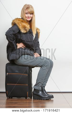 Happy young woman in warm jacket with suitcase. Gorgeous blonde tourist travel girl. Tourism.