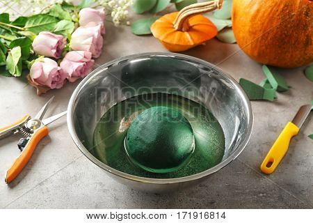 Pumpkin, oasis in bowl with water and tools on grey background