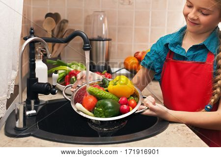 Young girl washing vegetables in a strainer under the water jet from the kitchen sink, shallow depth