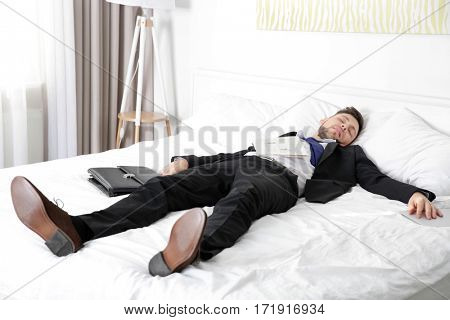 Dressed in business suit man fell asleep on bed in light room