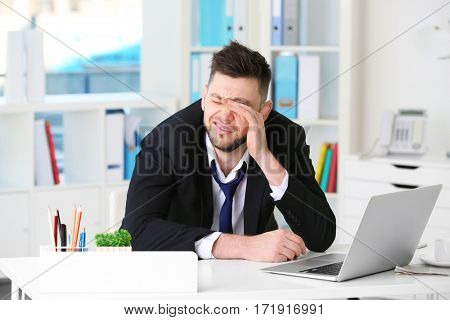 Young business man rubbing eyes sitting at workplace in office