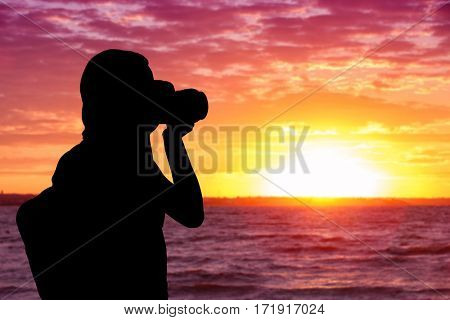 Silhouette of professional photographer taking photo of beautiful landscape during sunset