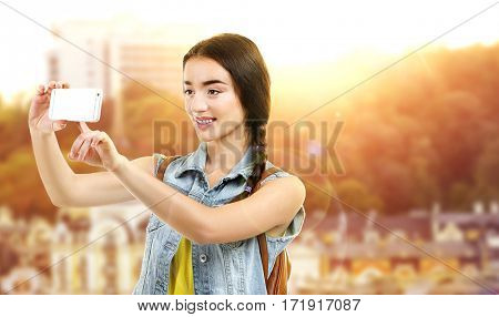 Young woman taking selfie on beautiful cityscape background