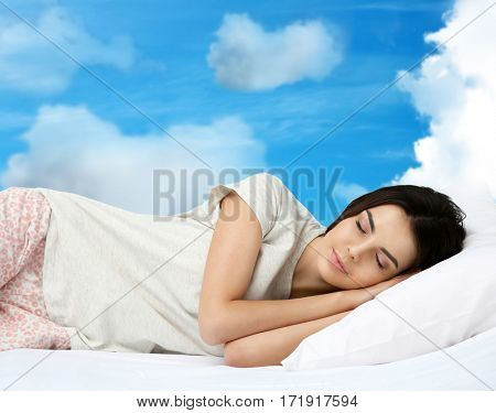 Young woman sleeping in bed and sky background