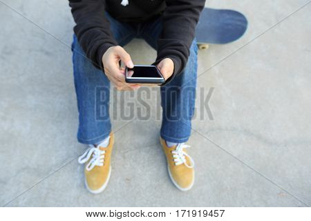 young skateboarder hands use cellphone at skatepark