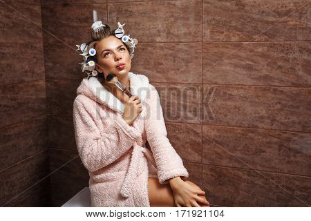 Young attractive housewife in the bathroom. A girl in a bathrobe and curlers doing morning makeup. Makeup Brush. Good morning. Dreaming.