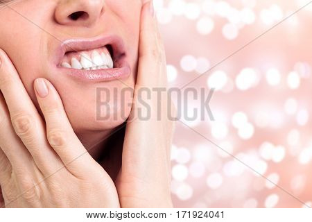 Woman with a toothpain on an abstract background with blurred lights