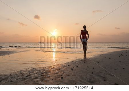 Slim woman on the water's edge watching the sun going down.
