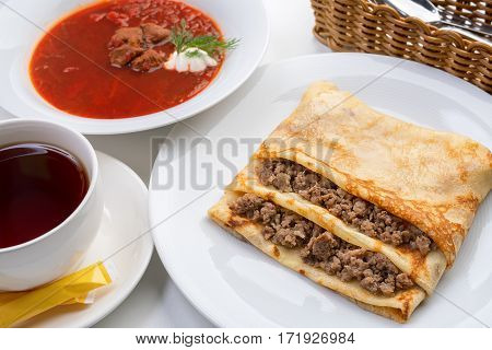 Pancake stuffed with meat and borsch with greenery and sour cream with cutlery in wicker plate and full cup of tea close up shot on white background.