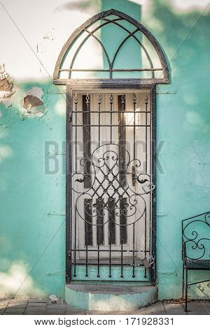 Door with iron gate on old green wall by sunset in Tel Aviv, Israel.