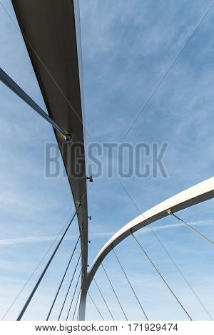 Closeup of a bidge support structure with blue and partly cloudy sky as background