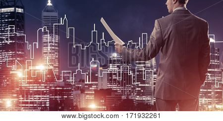 Rear view of businessman against modern cityscape holding papers in hand