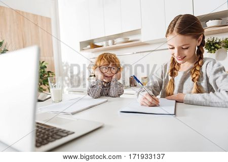 Gonna be like her. Diligent charming productive girl doing her homework while sitting at the table end enjoying the morning with her brother