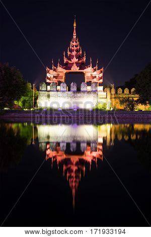 Gate bastion of a citadel of the Old city at night. Mandalay, Myanmar