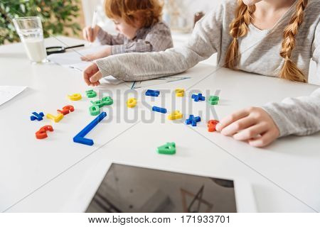 Academic fun. Clever curious enthusiastic lady learning math while arranging colorful plastic numbers and sitting with her brother at the table
