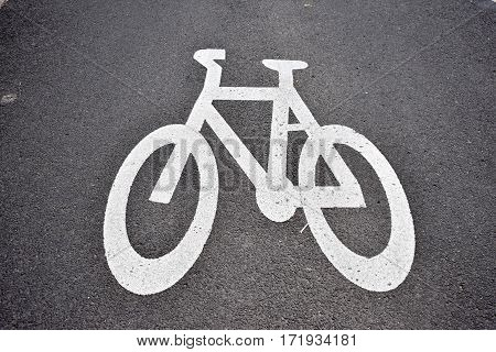 bicycle path stencil of white bike on grey pavement