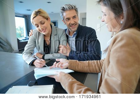 Clients signing sales agreement with real-estate agent