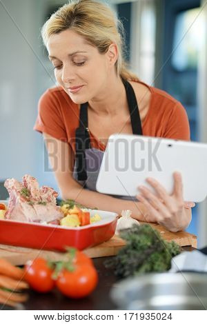 Woman in domestic kitchen reading cooking receipe on tablet