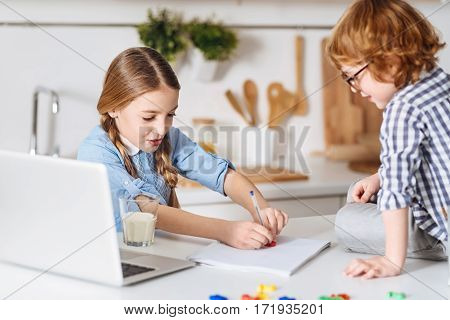 Home tutor. Charming intelligent pretty lady using special plastic numbers explaining her little brother some basic arithmetic while her watching her attentively and sitting at the tale beside her